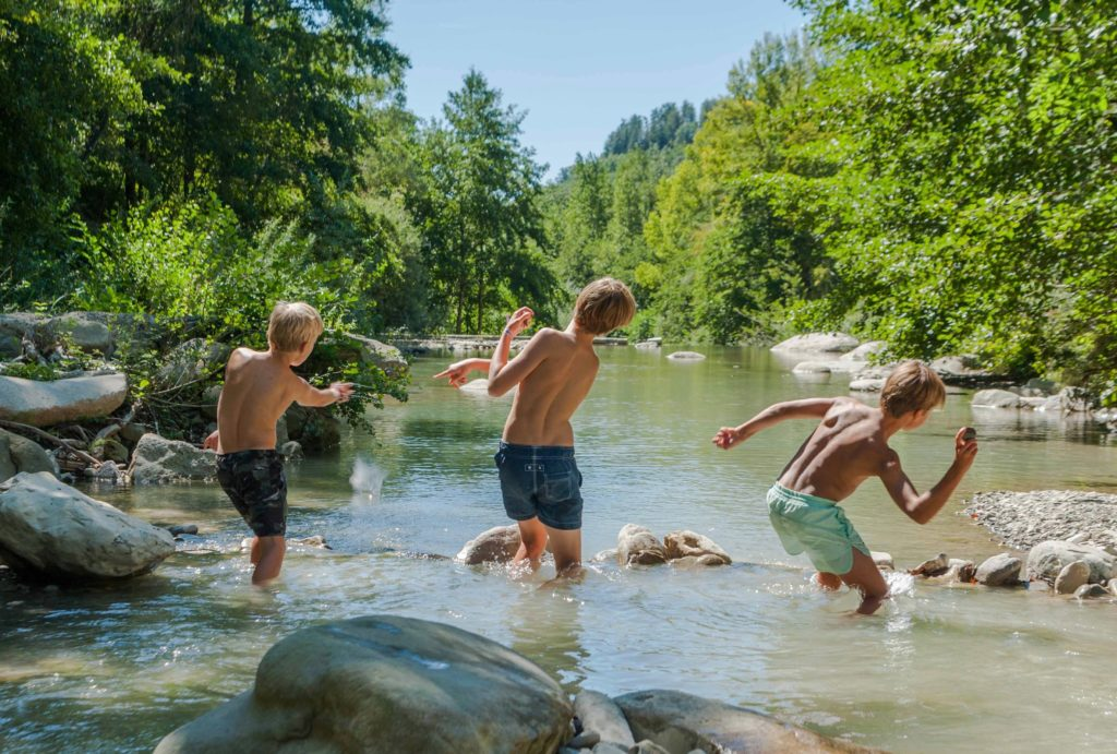 kids skipping stones in river